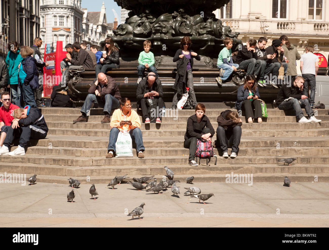 Tourists around the statue of Eros, Piccadilly Circus, London UK - Stock Image