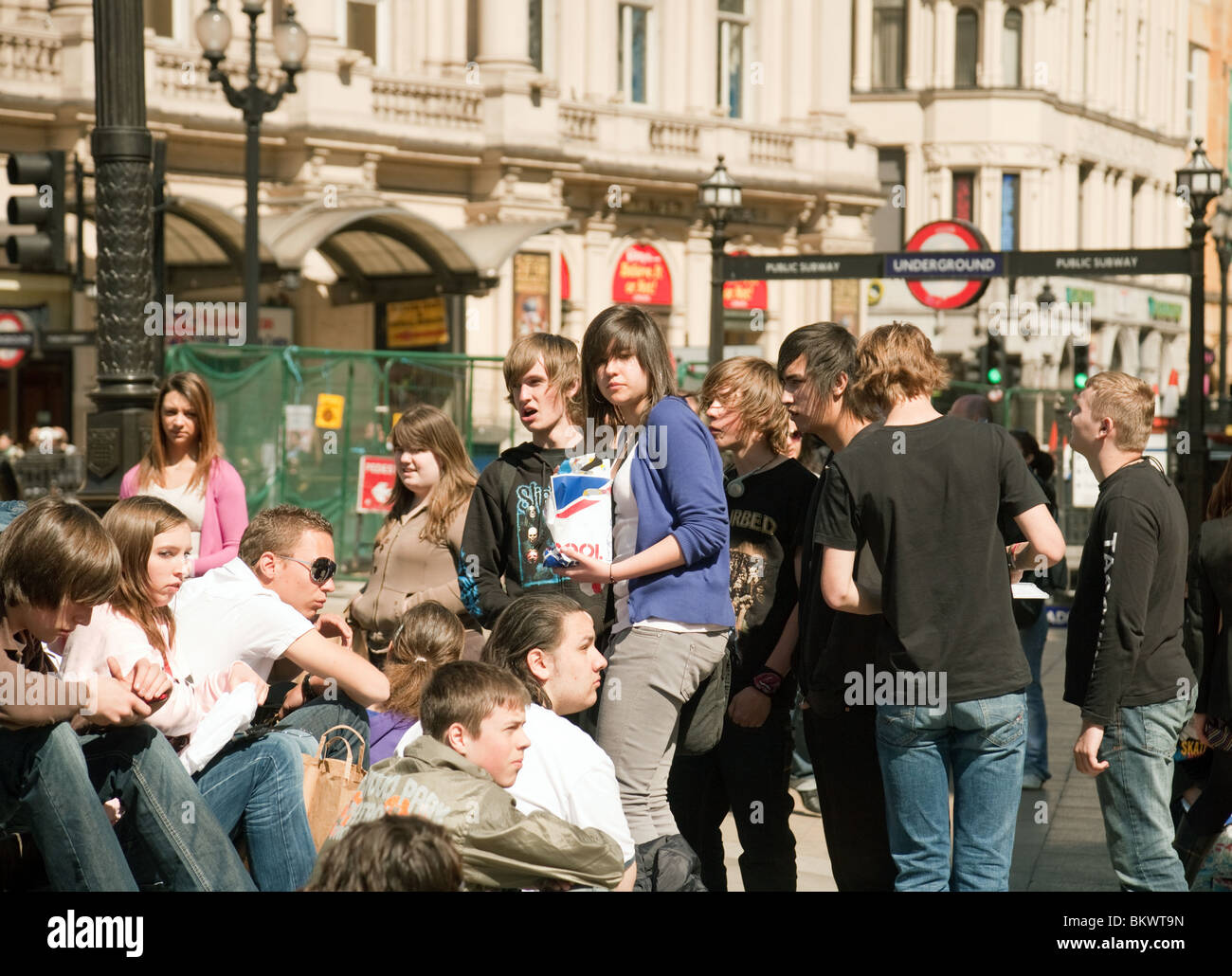 Teenagers in the crowd, Piccadilly Circus, Central London, UK - Stock Image