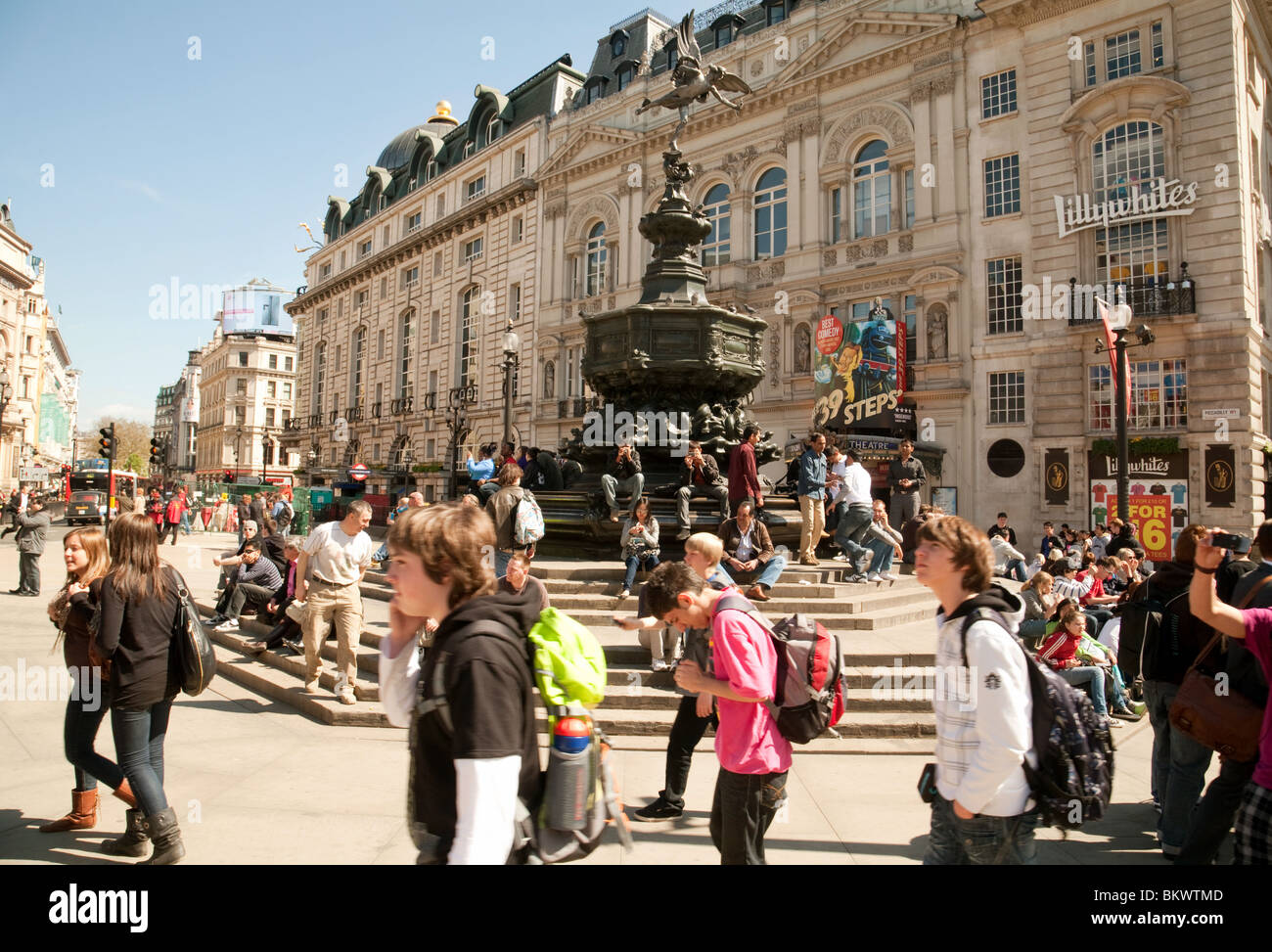 Teenage teenagers tourists around the statue of Eros, Piccadilly Circus, London UK - Stock Image