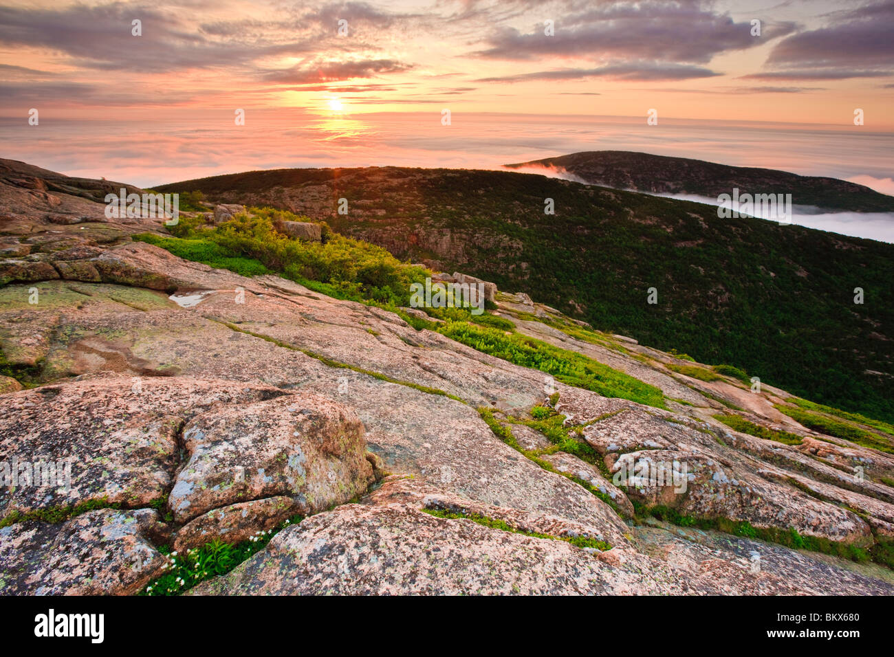 The sun rises above the fog as seen from the summit of Cadillac Mountain in Maine's Acadia National Park. - Stock Image