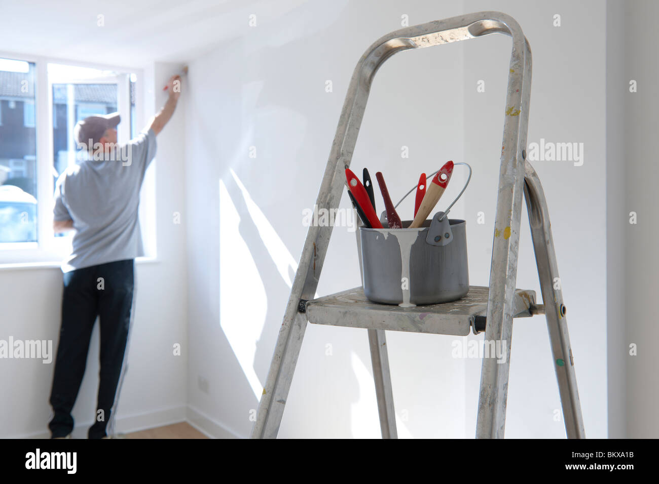 man decorating a room with ladder and paint pot in foreground - Stock Image