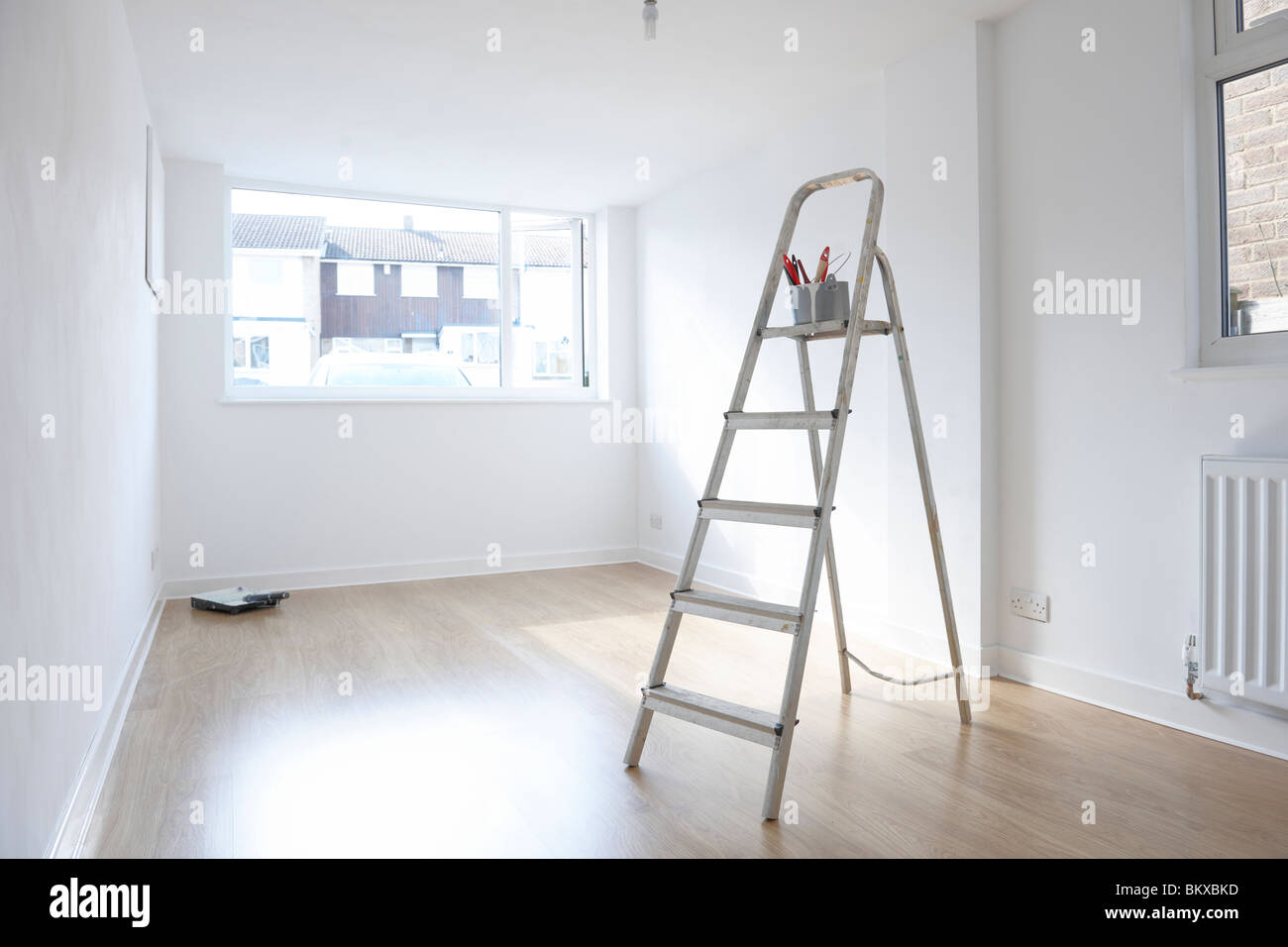 ladder with paint pot and brushes standing in empty room - Stock Image
