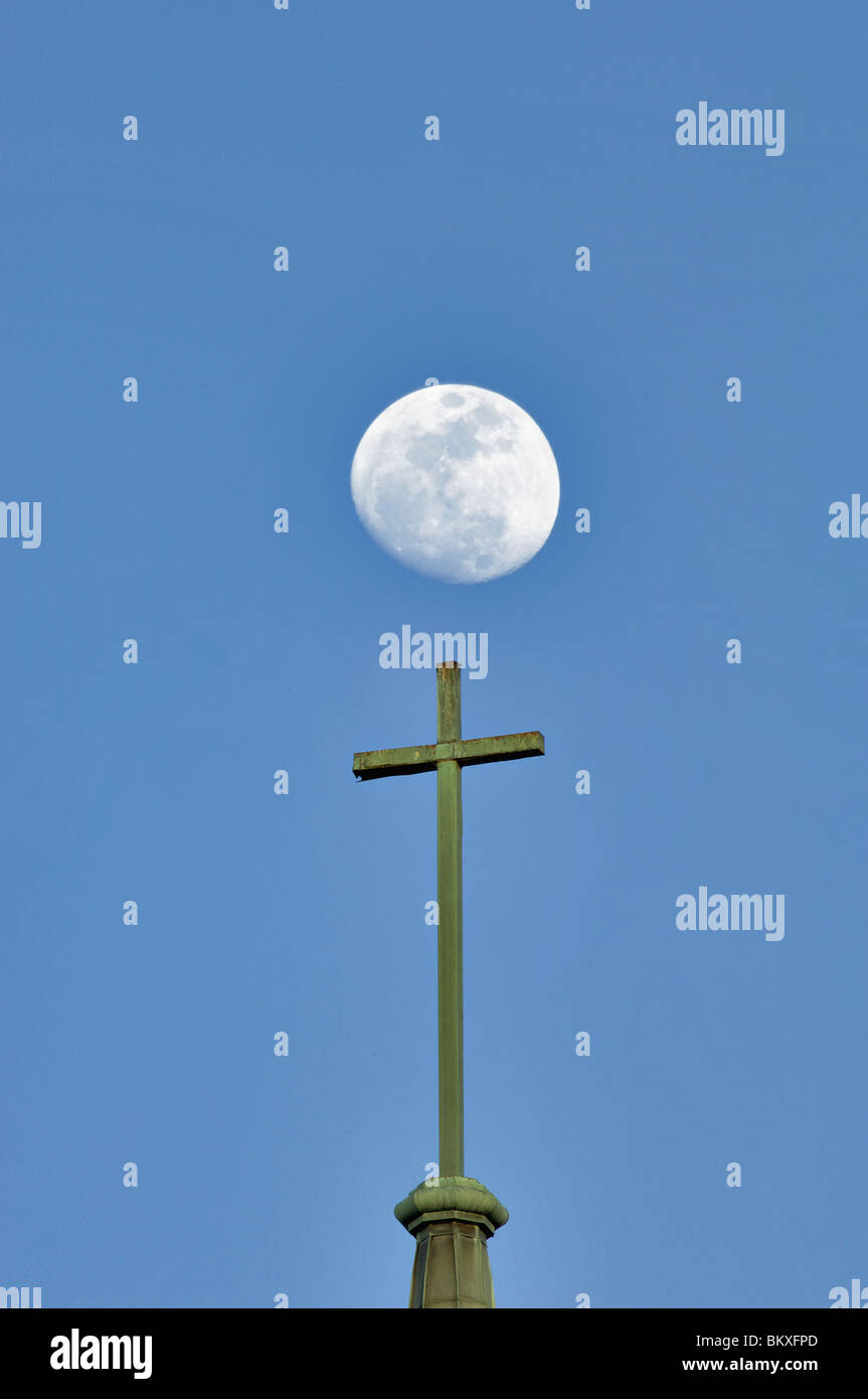 Christian Cross on Top of Church Steeple with Moon Behind in Kannapolis, North Carolina - Stock Image