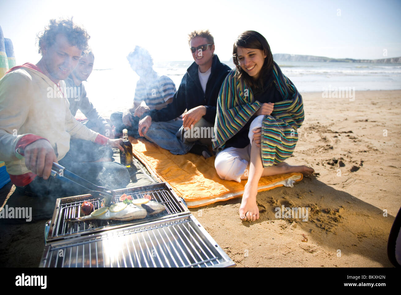 Group of friends sitting around a barbeque on the beach Stock Photo