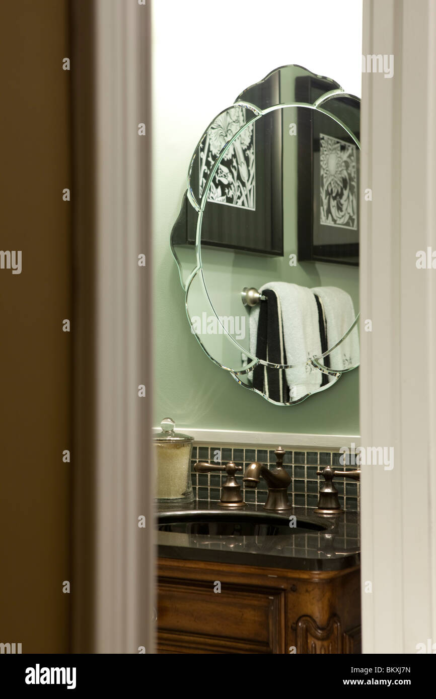 Small green guests bathroom view through open door. Mirror reflecting furnishings - Stock Image