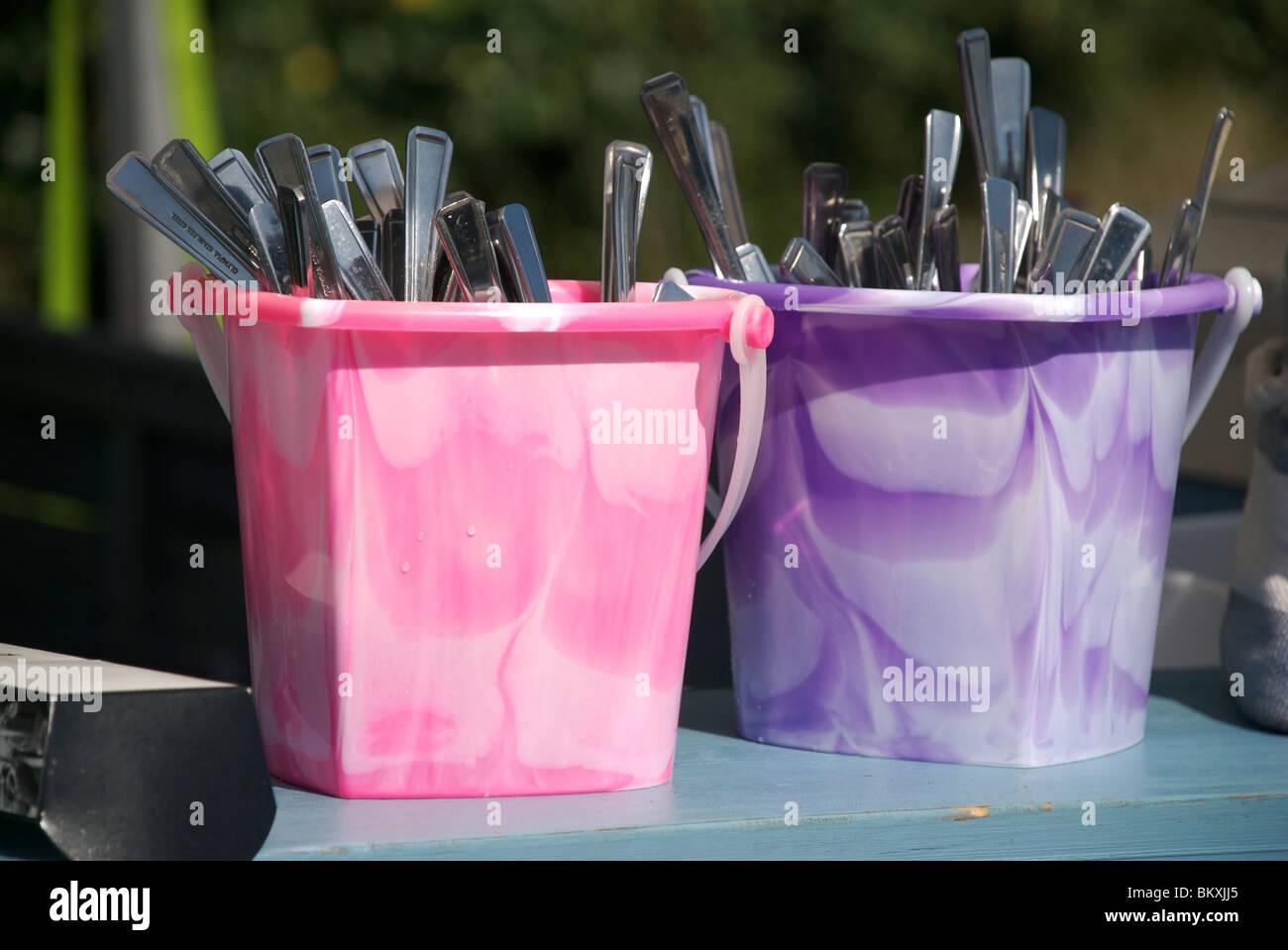 Colourful cutlery buckets, Salcombe, Devon, UK - Stock Image