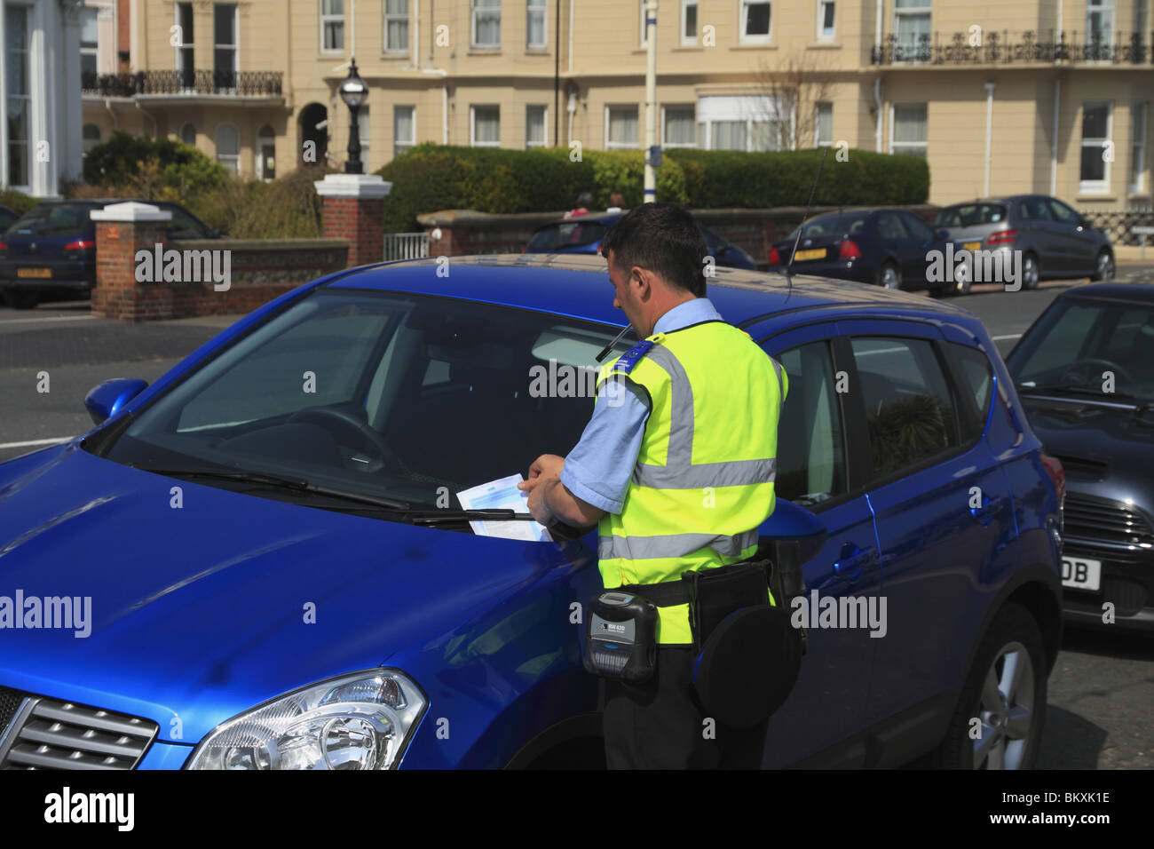 A car parking attendant fines a motorist for parking without a valid ticket at Eastbourne, East Sussex, England. - Stock Image