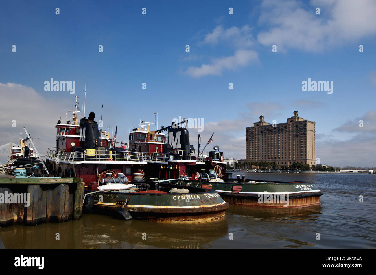 Tug Boats Docked near River Street on the Savannah River and View of Hutchinson Island in Savannah, Georgia - Stock Image