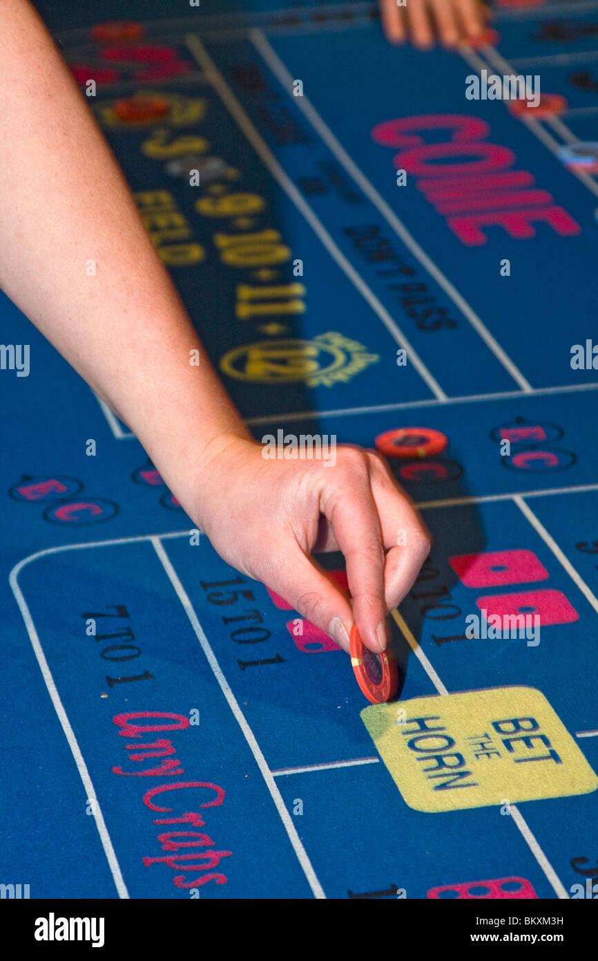 Scene on gaming floor of casino - woman places chip on craps table. South Lake Tahoe, Nevada, USA. - Stock Image