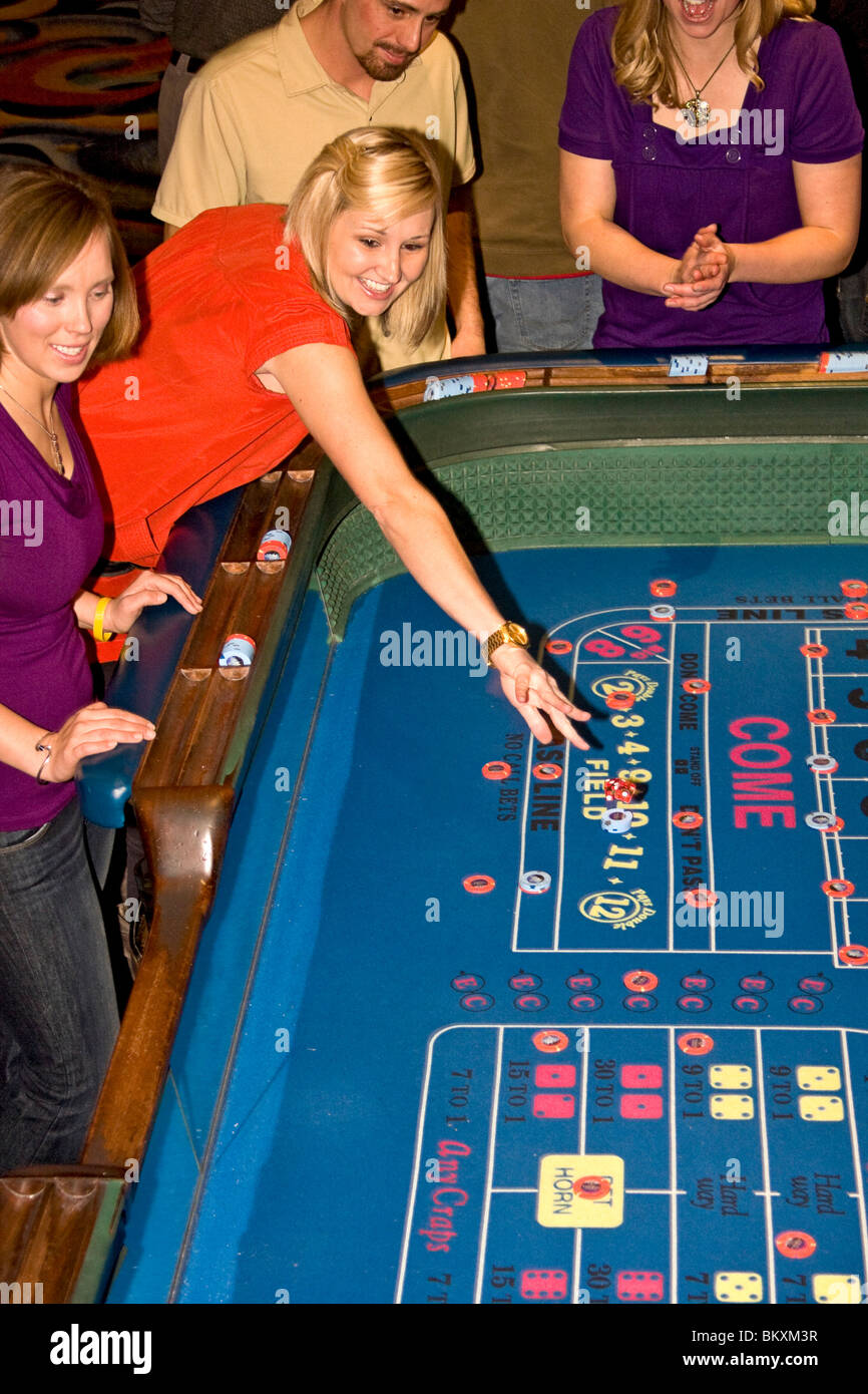Scene on gaming floor of casino - excited woman throws dice at craps table. South Lake Tahoe, Nevada, USA. - Stock Image