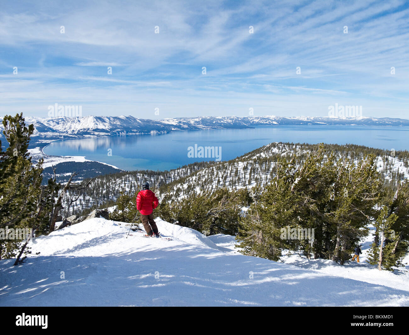 Skier admires view of Lake Tahoe from the ski slope of Heavenly Mountain Resort, USA. Winter - Stock Image