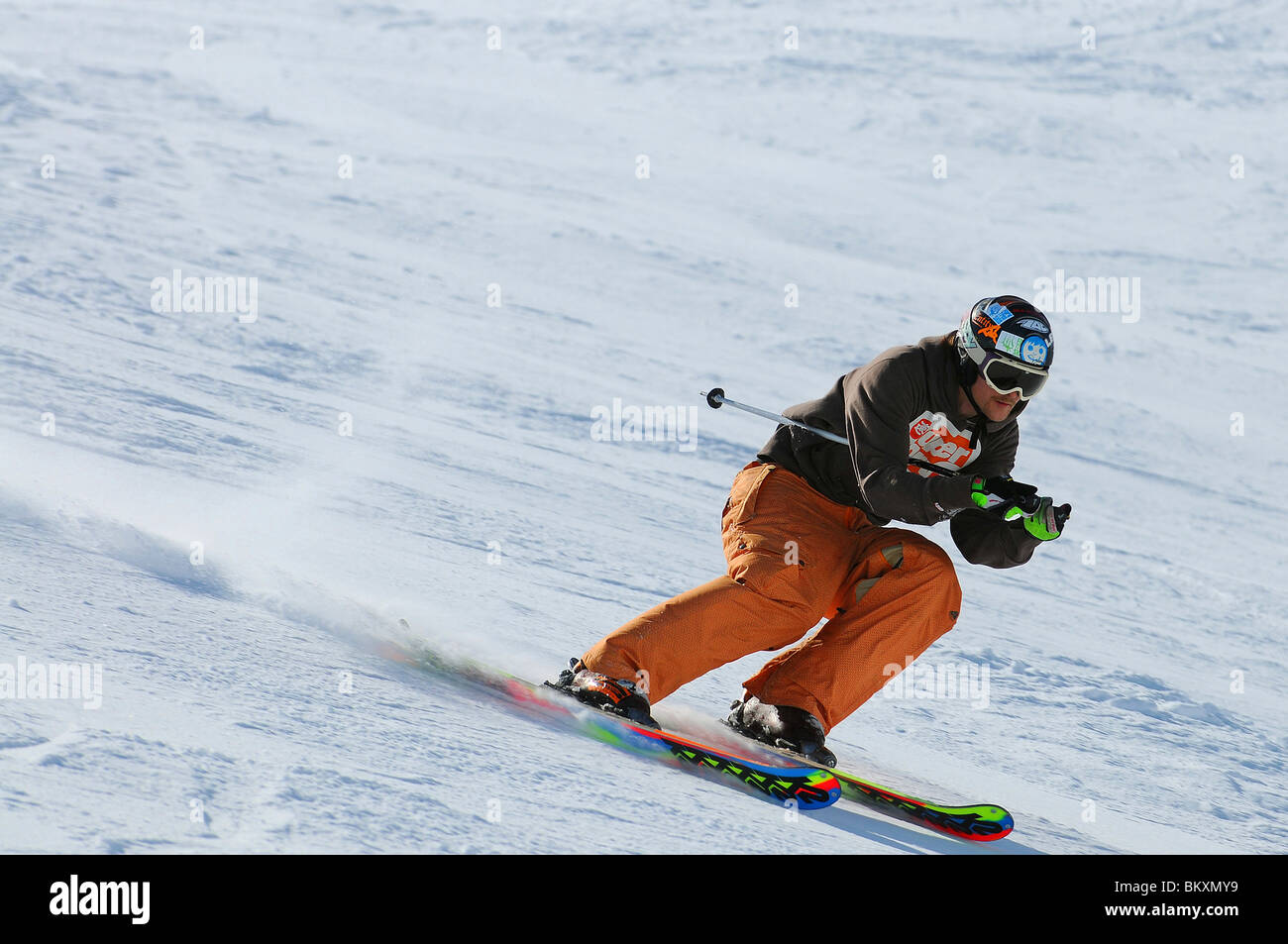 A downhill skier at speed on piste in Courchevel in the French Alps - Stock Image