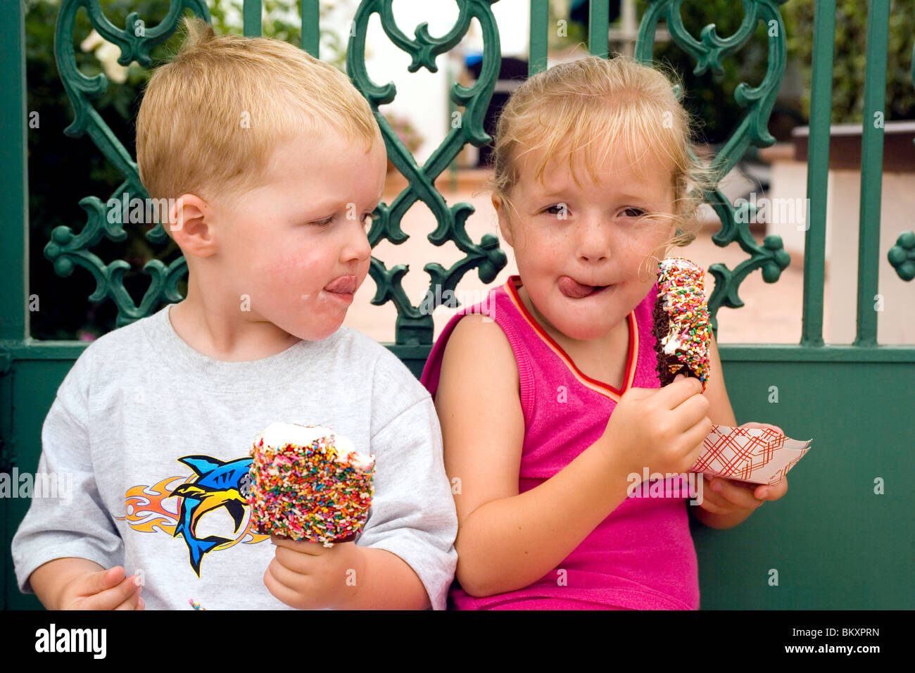 A young brother and sister enjoy Balboa Bars, a traditional and tasty ice cream treat on Balboa Island in Newport - Stock Image