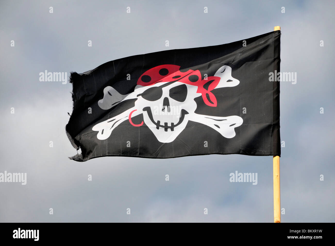 a black pirate skull and cross bone flag flying from a mast. - Stock Image