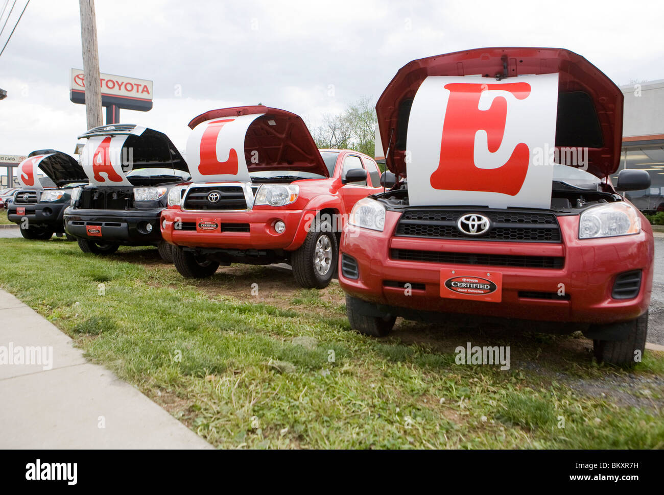 Toyota vehicles on a dealership lot with a 'Sale' sign.  - Stock Image
