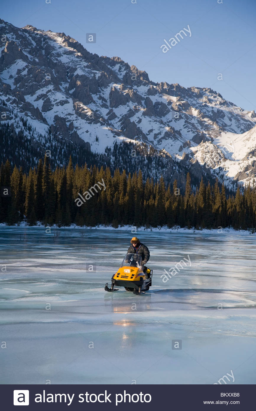 A snowmobiler negotiates overflow ice on a trail in the White Mountain National Recreation area, Interior Alaska. - Stock Image