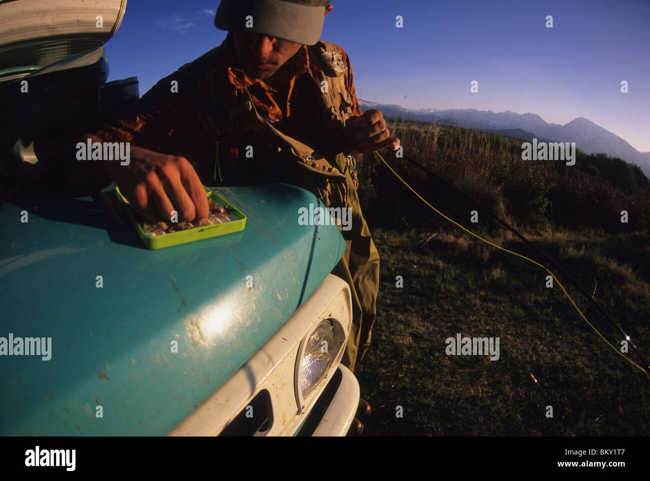 A man picks a fly from his fly box while  fishing in Bishop, California. - Stock Image