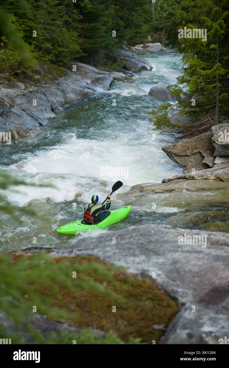 A whitewater kayaker sets up for a drop on a high mountain river. - Stock Image