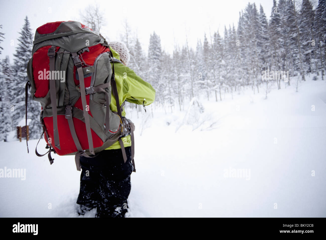 A young woman hikes with a backpack in fresh powder in the Wasatch Mountains, Utah. - Stock Image