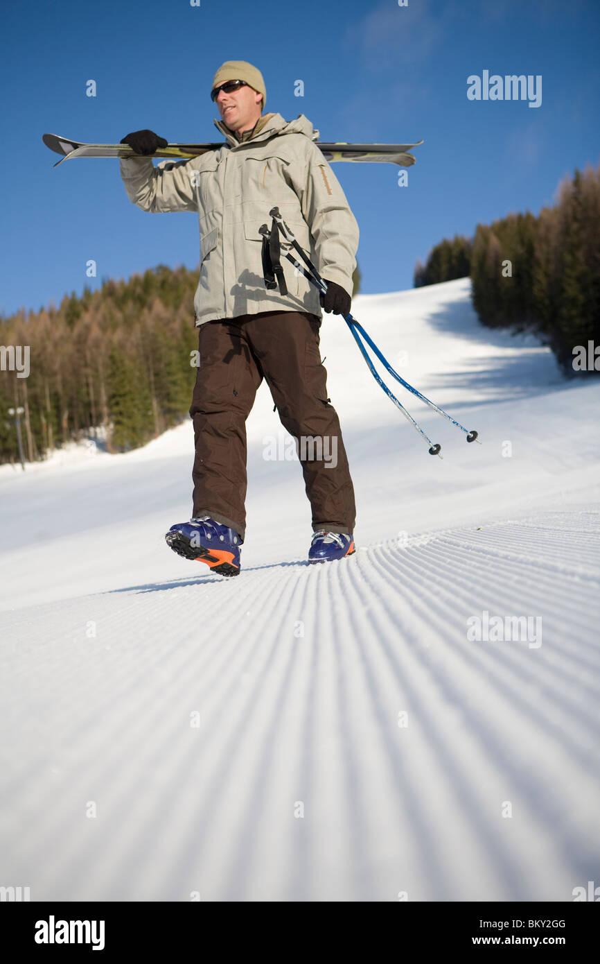Male skier walk across freshly groomed ski slope. - Stock Image