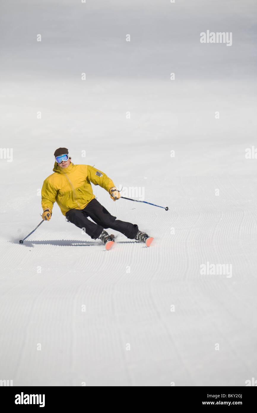 Male skier tears up freshly laid corduroy ski run. - Stock Image
