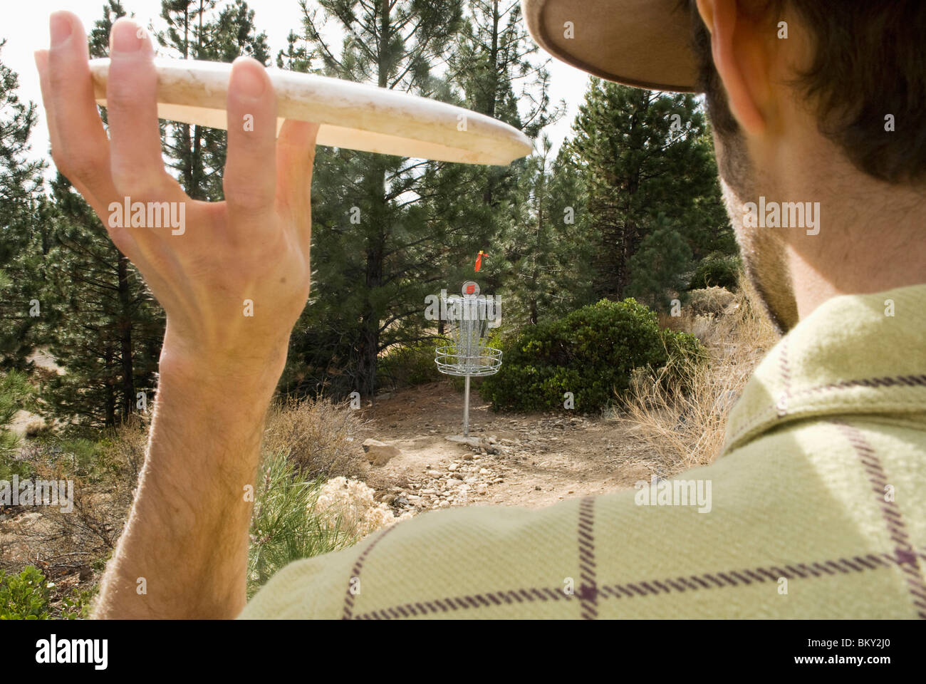 A young man perfects the pizza toss during a game of disc golf in Lake Tahoe, California. - Stock Image