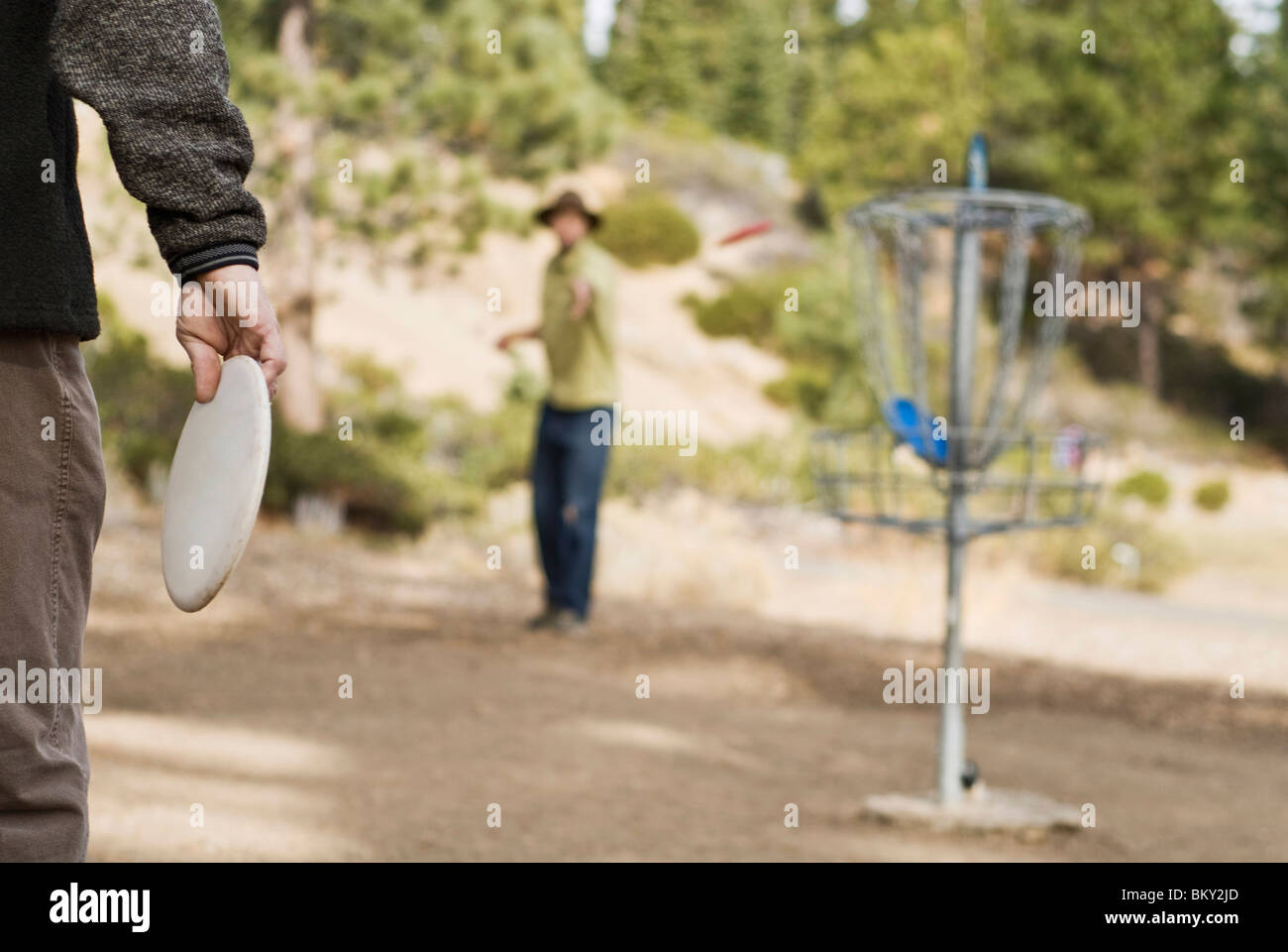 Before playing a game of disc golf, a young man warms up on a practice basket in Lake Tahoe, California. - Stock Image