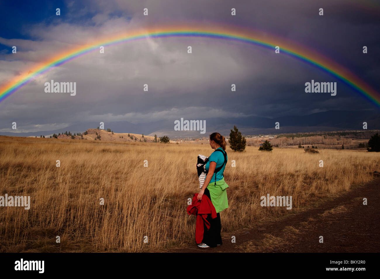 Mother and newborn baby with a rainbow over the grass, hills and trees of Blue Mountain, Missoula, Montana - Stock Image