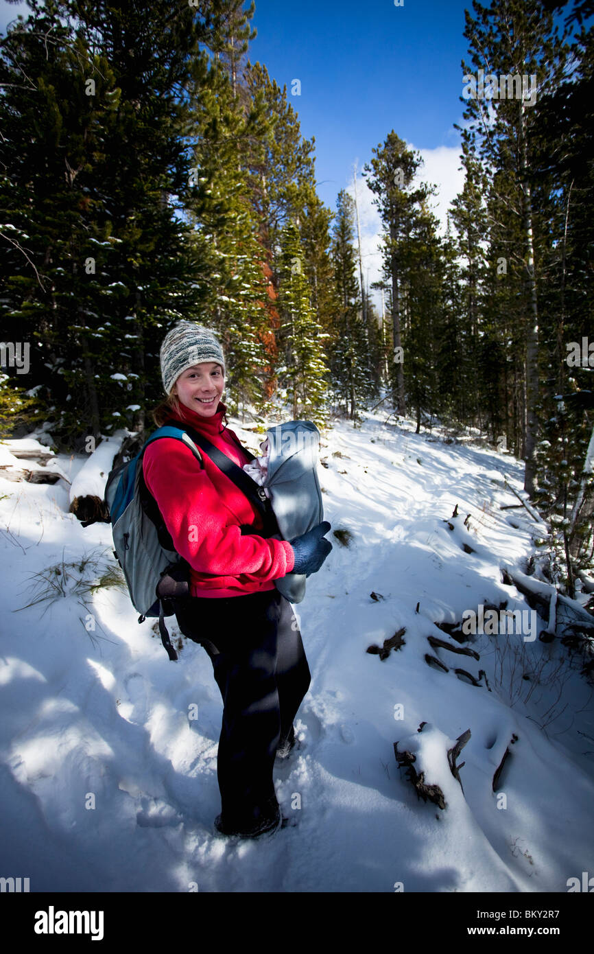 Mother and newborn baby in a front carrier on a snowy hiking trail in winter, Bitterroot Wilderness, Montana. - Stock Image