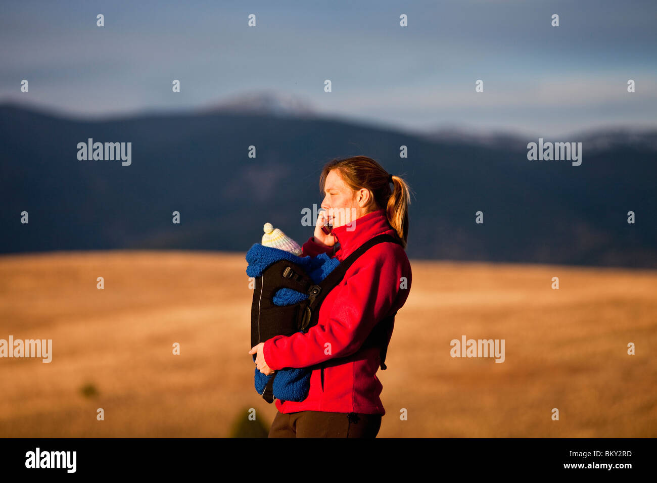 Mother on cell phone and newborn baby in front carrier while hiking through grassy hills, Water Works, Missoula, - Stock Image