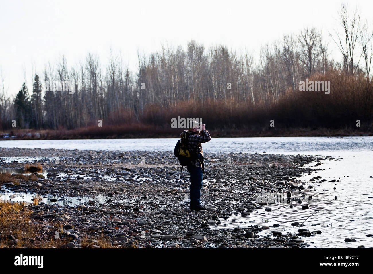 Young man in a camouflage hat wearing a backpack using binoculars at a rivers edge, Florence, Montana. - Stock Image