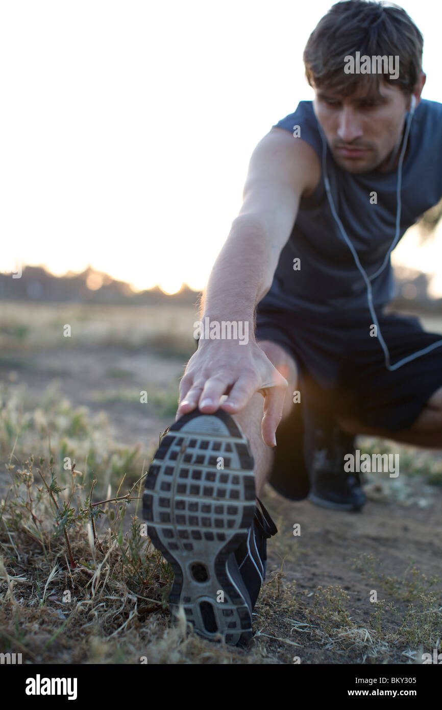 Man in his late 20's stretching before running it an open field in San Diego, California. - Stock Image