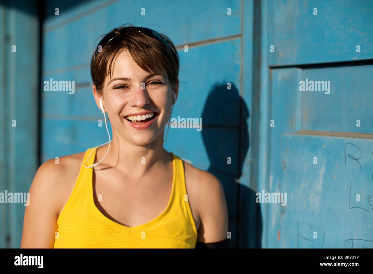 Woman in her late 20's wearing her workout clothes and headphones looks at the camera and smiles in San Diego, - Stock Image