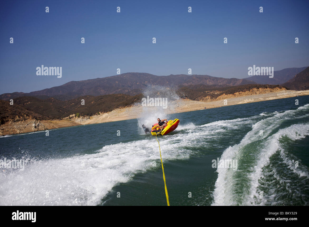 People tubing in Castaic Lake, Santa Clarita, California are about to flip over. - Stock Image