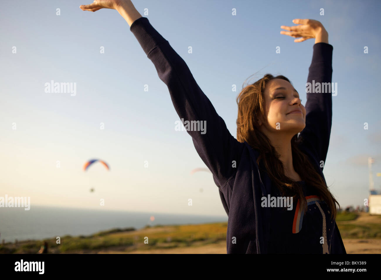 Female in her early 20's throws her arms up and closes her eyes to feel the wind at a paragliding port in California. - Stock Image