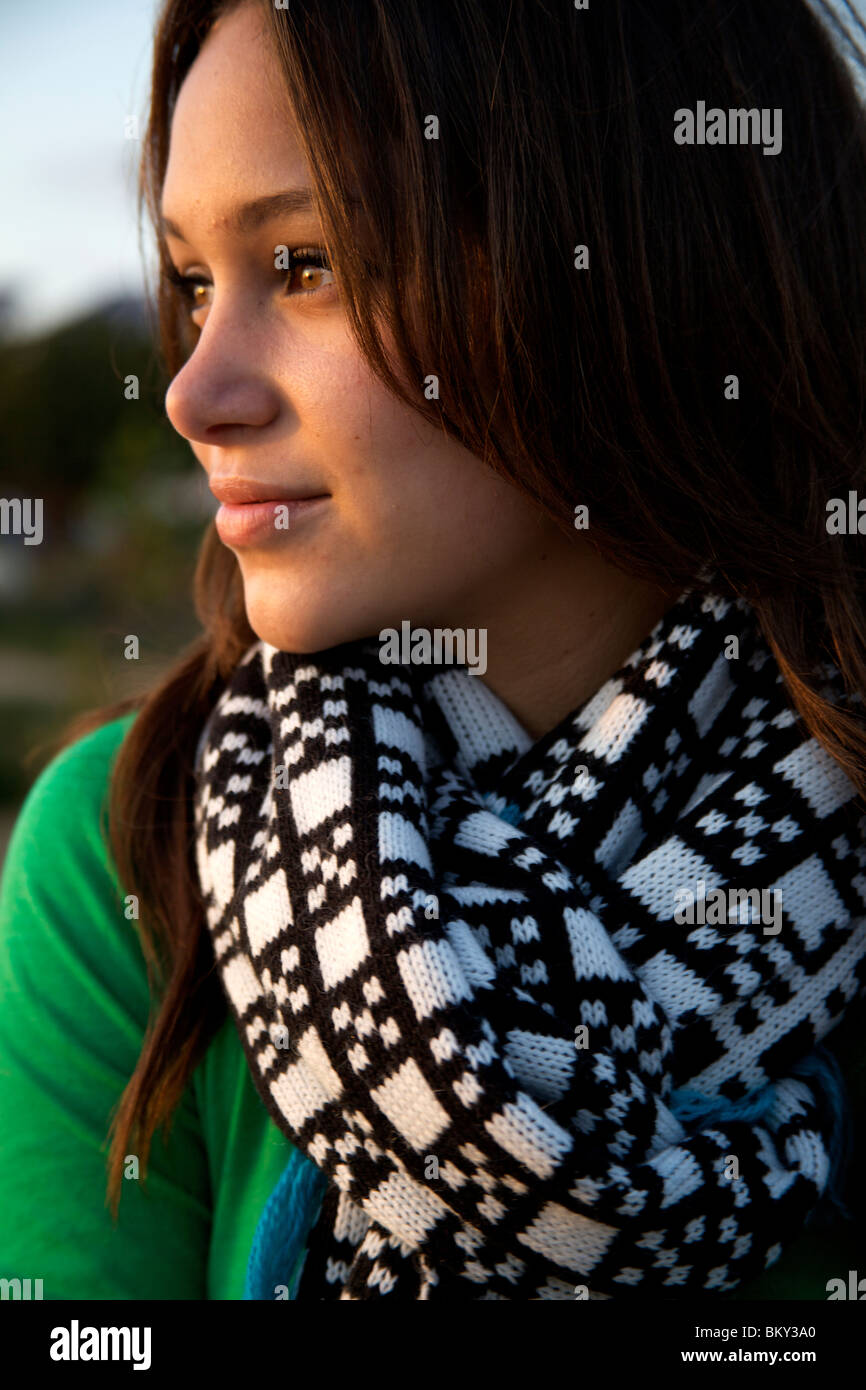 Close-up shot of young female wearing scarf watching the sunset. - Stock Image
