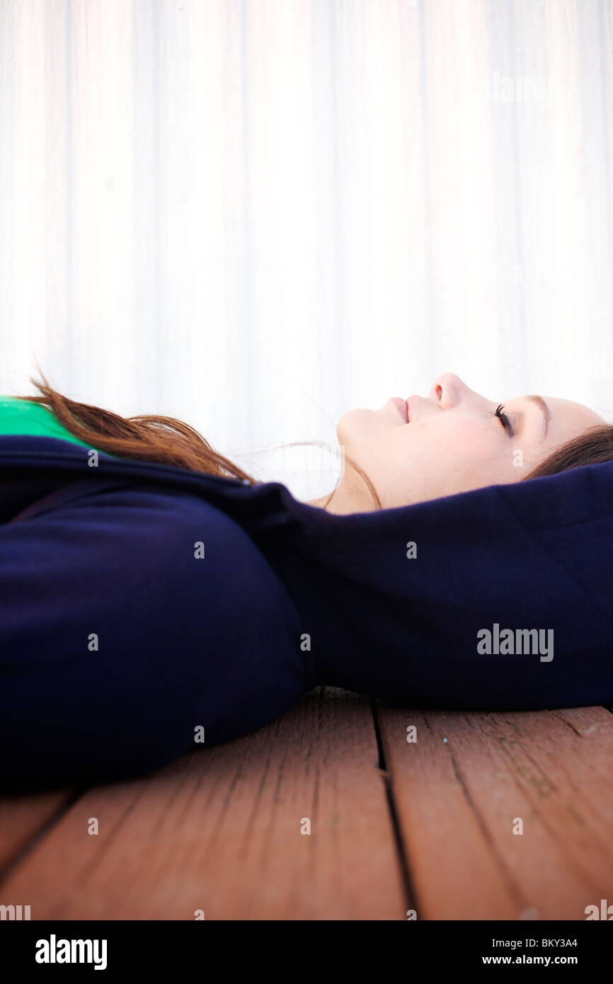 Female in her early 20's lays on the floor and closes her eyes . - Stock Image