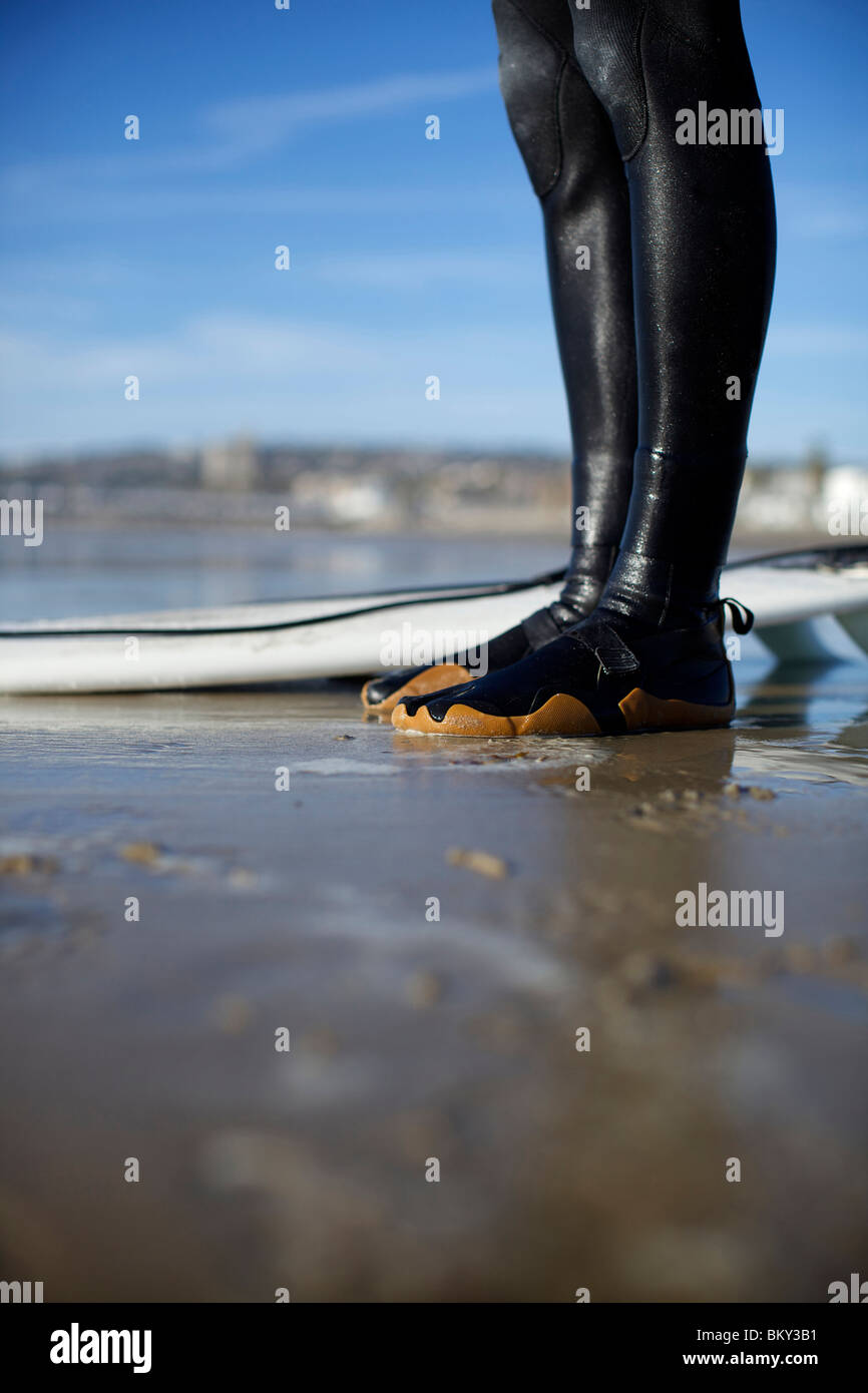 Surfer's wet feet in his booties on wet sand by the surfboard on a sunny day in Pacific Beach, San Diego. - Stock Image