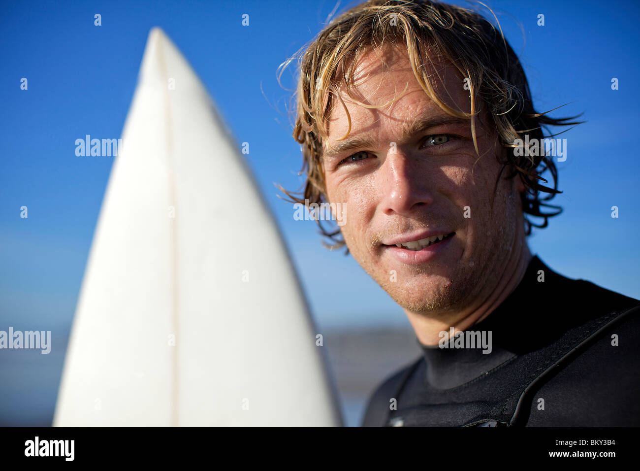 Young male surfer with wet hair at Pacific Beach in San Diego, California on a sunny day looks straight at the camera - Stock Image