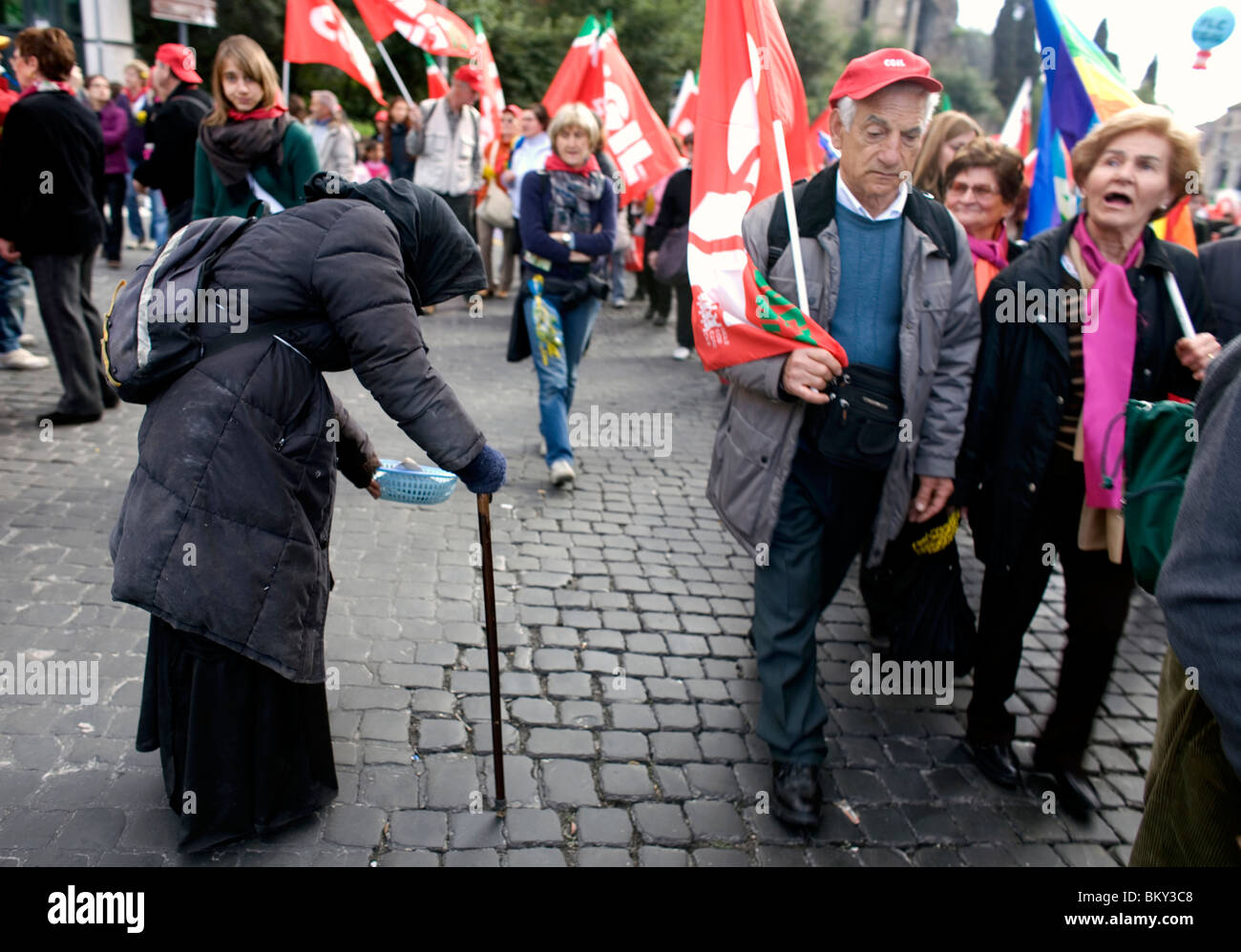 A woman begs for money as a political march passes her by in Rome, March 8, 2008. Photo/Chico Sanchez Stock Photo