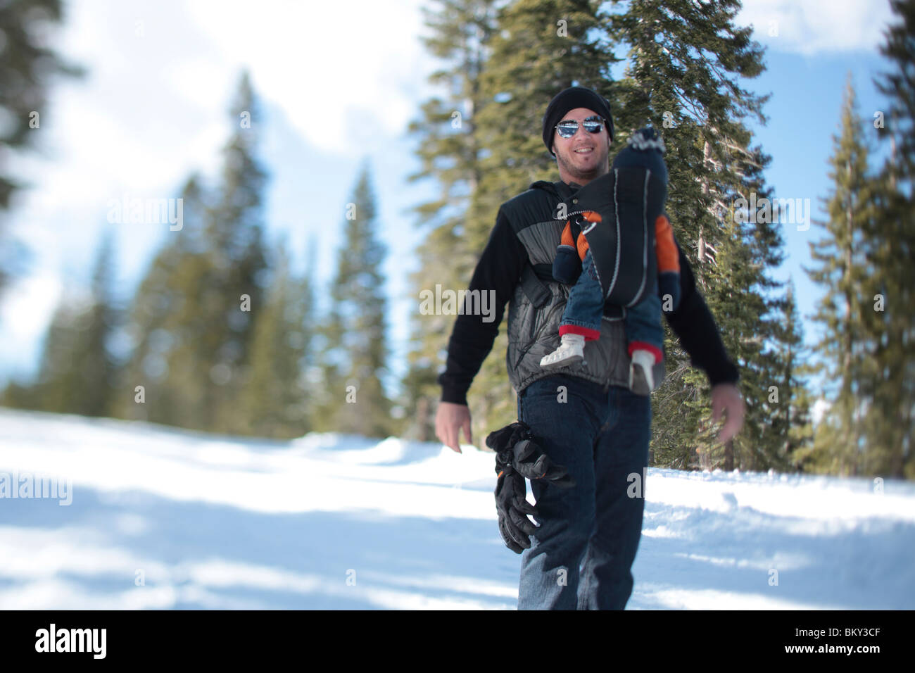 A father, age 35, walks with his son, age 4 months, in the snow covered wilderness of Lake Tahoe, Calfornia. - Stock Image