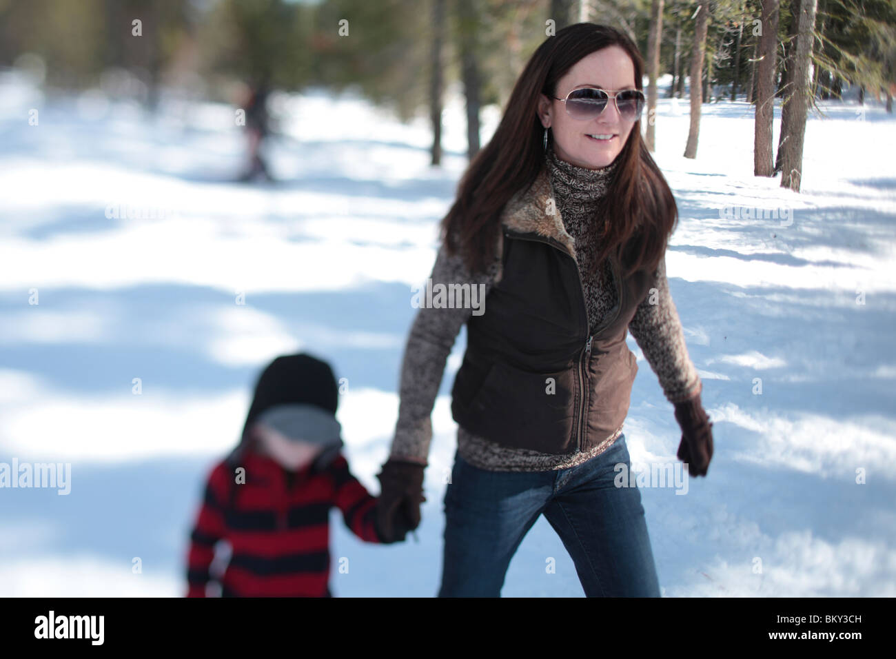 A mother snowshoes with her 4 year-old son in the snow covered wilderness of Lake Tahoe, Calfornia. - Stock Image