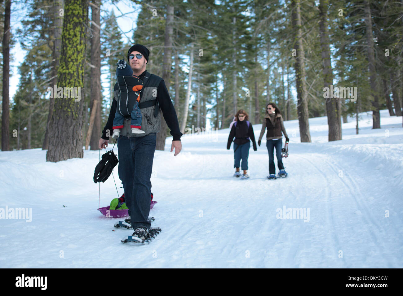 Two families snowshoe with infants and toddlers in the snow covered wilderness of Lake Tahoe, Calfornia. - Stock Image