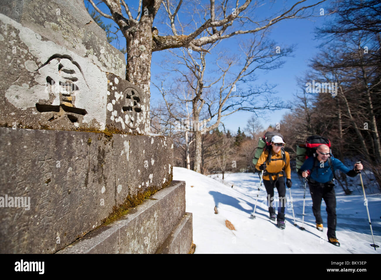 Two people are hiking on a trail next to a wall with Japanese characters on it in Mount Fuji National Park, Honshu, - Stock Image