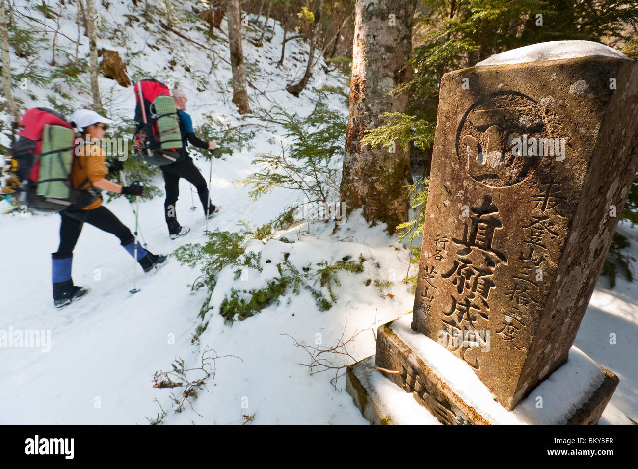 Two people are hiking on a trail next to a pillar with Japanese characters on it in Mount Fuji National Park, Honshu, - Stock Image