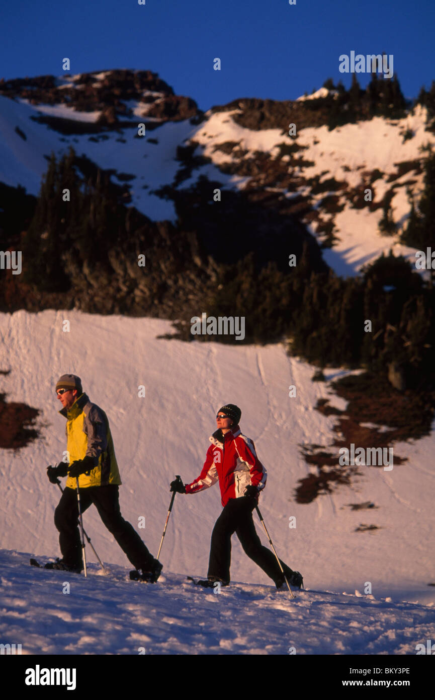 Couple snowshoeing on snowy mountain flanks in Mt. Rainier National Park, Washington. - Stock Image
