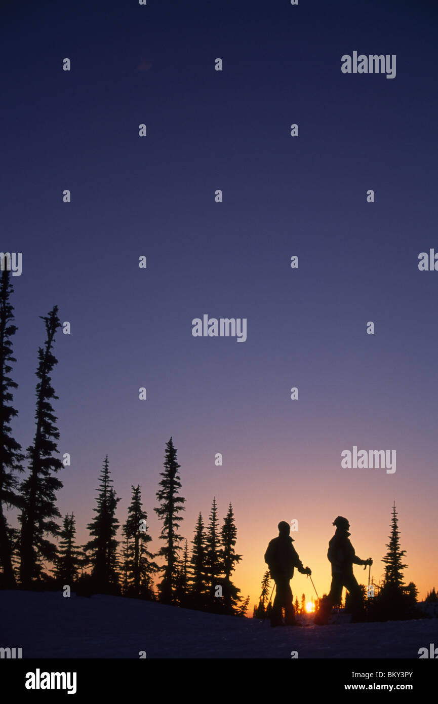 Couple snowshoeing during a colorful sunset in Mt. Rainier National Park, Washington. - Stock Image