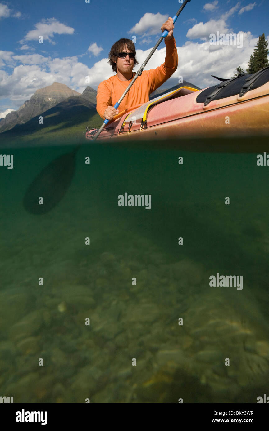 Solo paddler sea kayaking on a remote lake in Glacier National Park. - Stock Image