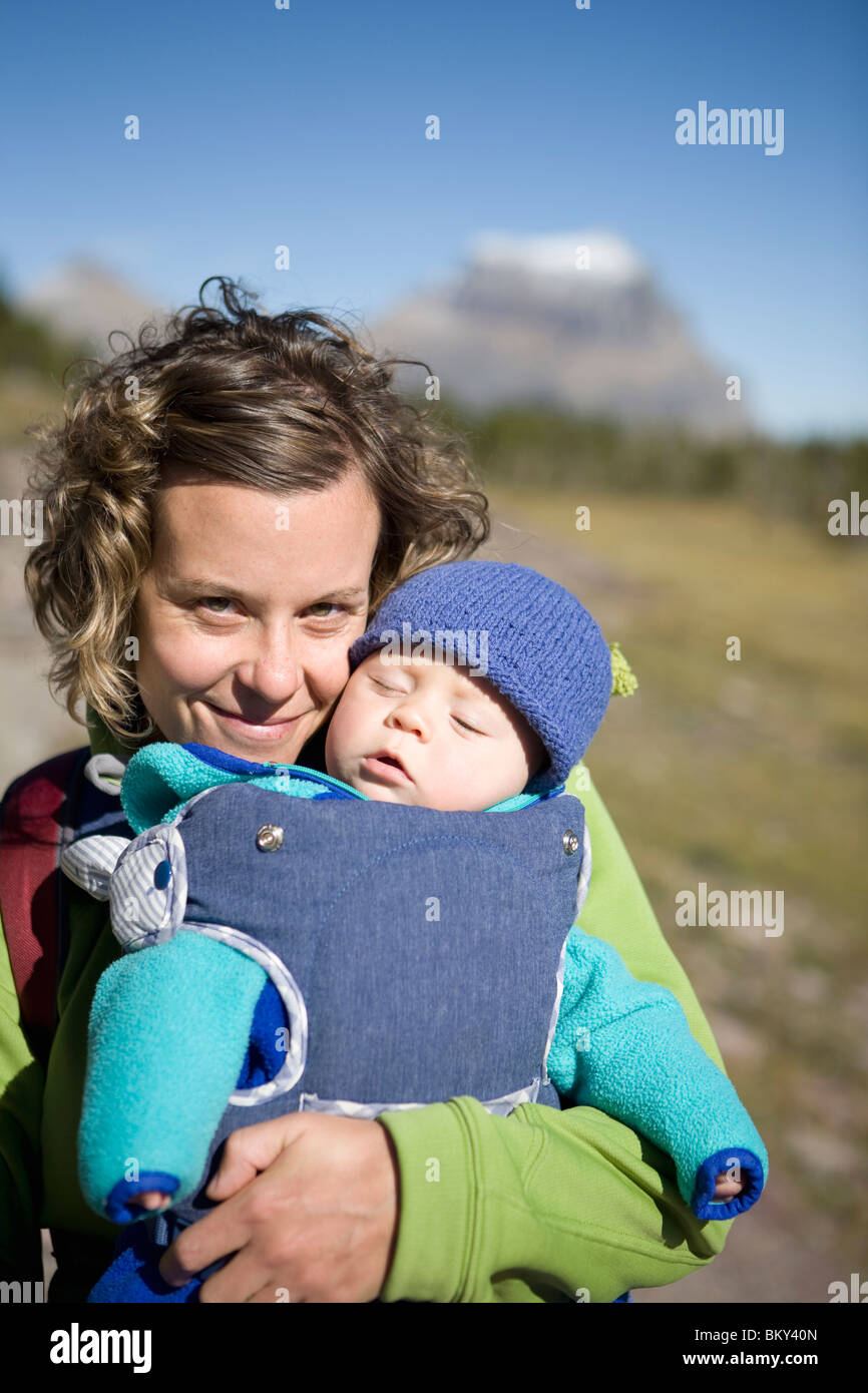 Mother and baby hiking on a boardwalk trail at a pass in the Rocky Mountains. - Stock Image