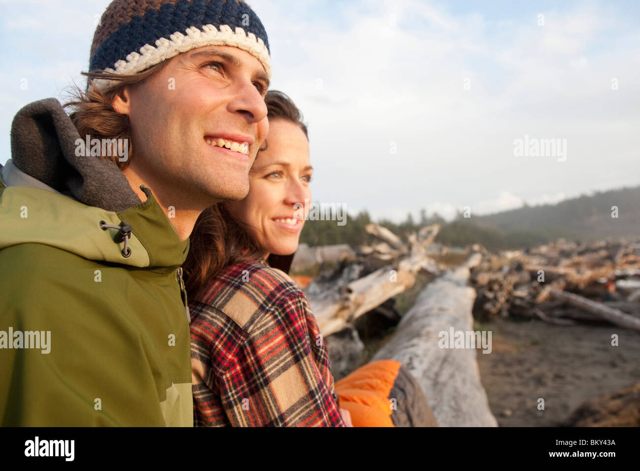 A young couple smiling while watching the sunset on the coast. - Stock Image